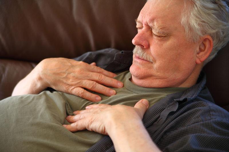 High angle view of senior man sleeping on sofa at home