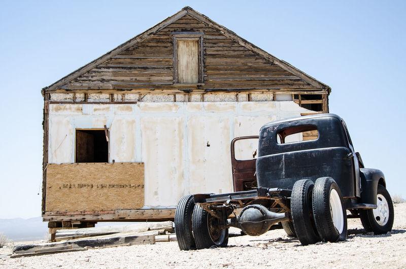 Abandoned vintage car on land against sky