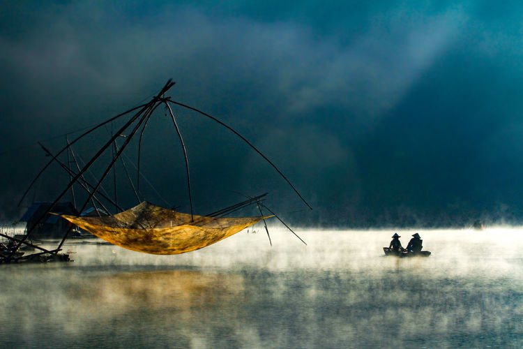 Fishermen sailing in boat by fishing net in sea against storm clouds