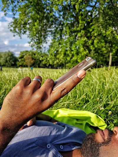 One Person Human Body Part Real People Low Section Close-up Grass Tree Nature Human Hand Cellphone Mobile Phone Man With A Phone Technology Communication Outdoors Man In The Park Man Using His Phone Internet Searching Black Man Face Part Man's Hands