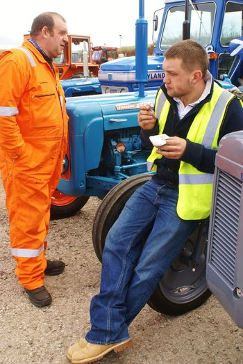 At lunch in Hatton Boilersuit Casual Casual Clothing Composition Flourescent Orange Collar Friendship Front View Happiness Holding Human Leg Jeans Jeans Leisure Activity Lifestyles Lunchtime Men Occupation Real People Sitting Snack Time! Standing Tractor