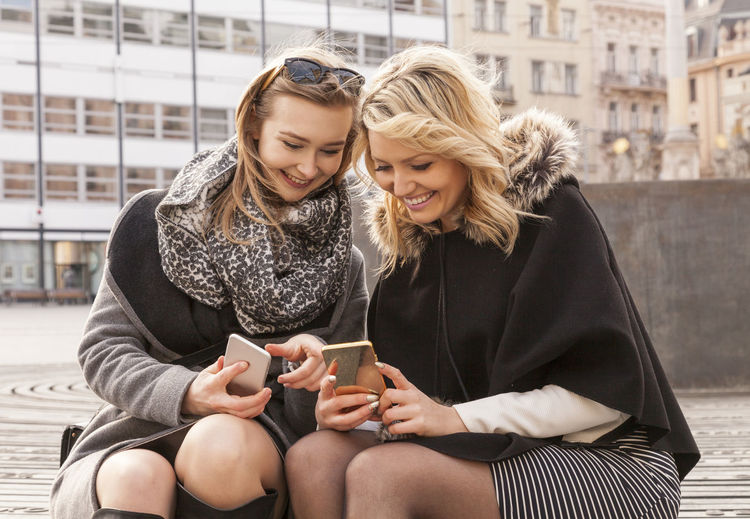 Friends Using Mobile Phone While Sitting In City