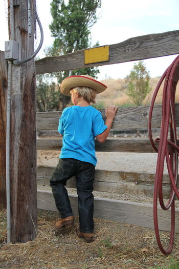 Boy standing in front of wooden gate with cowboy hat