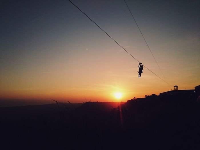 Silhouette Of One Woman On Zip Line