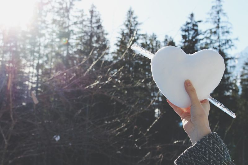 Midsection of woman holding heart shape in winter
