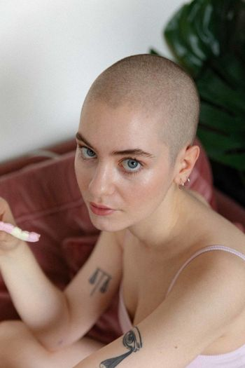 Portrait of bald young woman sitting at home