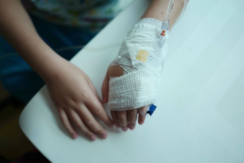 High angle view of woman with iv drip and bandage on hand sitting at clinic