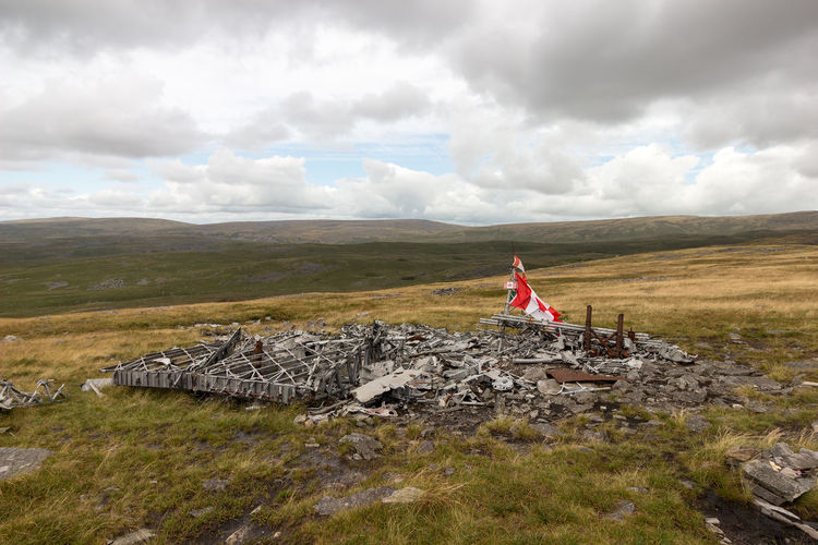 Scenic view of canadian flag on landscape against sky. wreckage of wellington bomber mf509