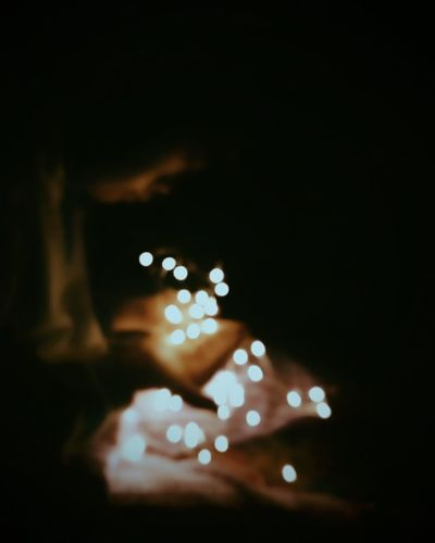 Defocused image of hand holding illuminated lights at night