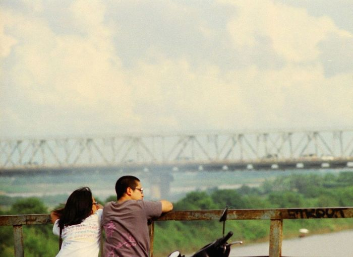 People standing on railing against sky