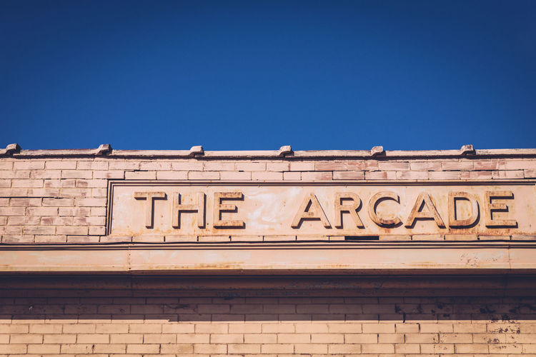 Low angle view of the arcade sign on building against clear sky