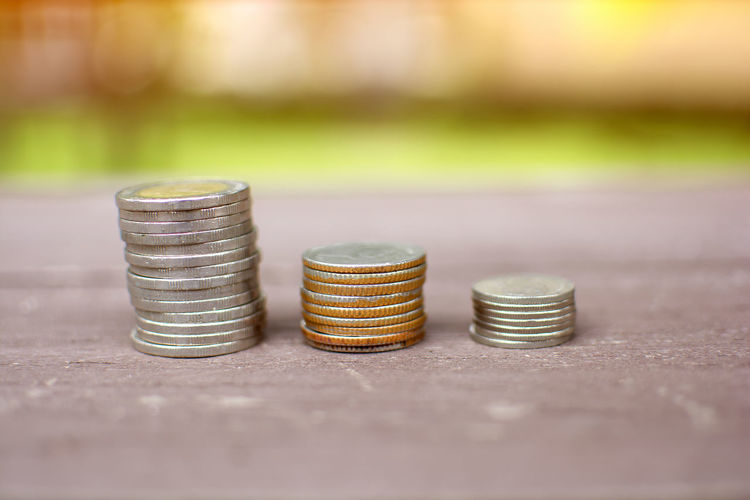 Coins stack growing business on wooden table with blur background Growth Rich Thai Trading Coin Currency Day Finance Focus On Foreground Graph Growth Metal Money No People Outdoors Pile Saving Saving Money Savings Tower Towers Wealth Wealthy