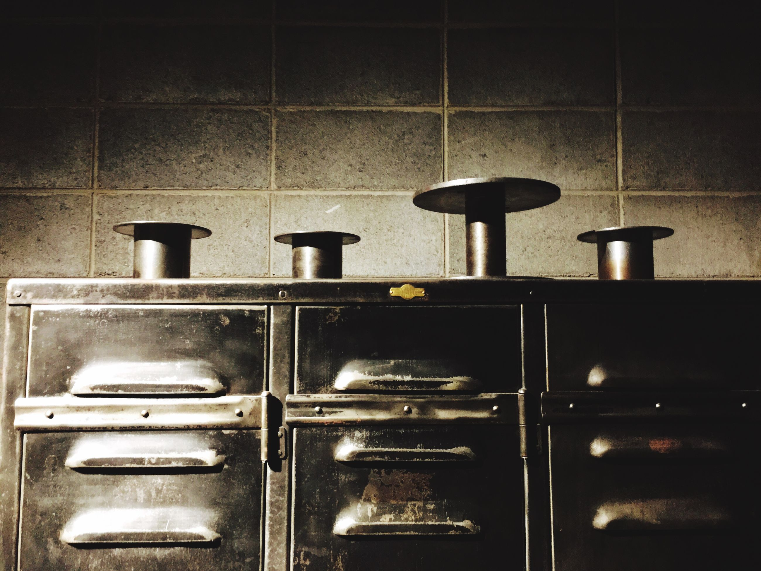 indoors, no people, metal, wall - building feature, still life, close-up, old, household equipment, domestic room, architecture, kitchen utensil, group of objects, wood - material, day, tile, built structure, illuminated, shelf, saucepan