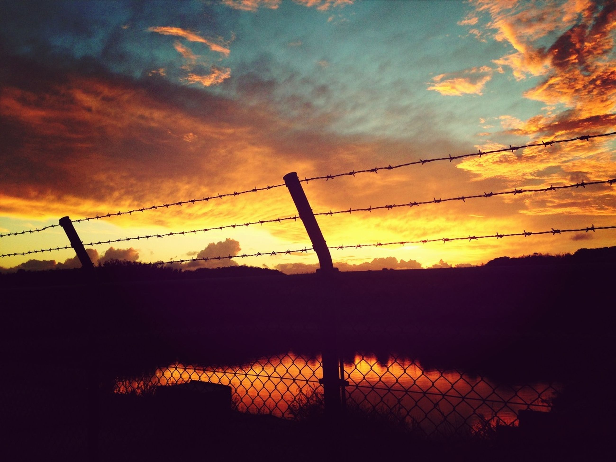 sunset, silhouette, sky, cloud - sky, fence, orange color, safety, protection, connection, security, low angle view, cloud, cloudy, nature, tranquility, beauty in nature, railing, dramatic sky, metal, scenics