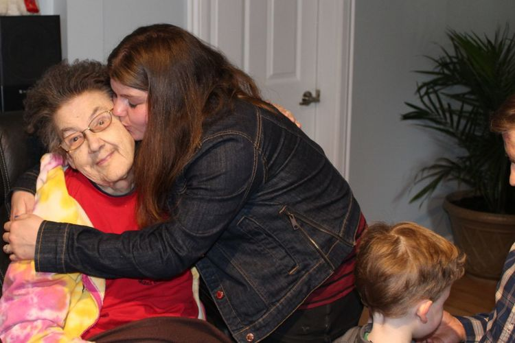 Granddaughter kissing grandmother sitting on chair at home