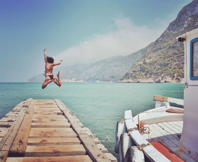 Rear view of young woman diving into sea from pier against sky