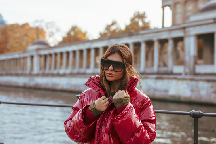 Woman wearing sunglasses standing by railing against bridge
