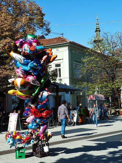 European Cities Novi Sad Serbia Eastern Europe Balkans Europe Outdoors Sunlight And Shadow Cityscape City Life Public Places Building Exterior Architecture Built Structure Day Building Street Photography City Real People Sunlight Tree Men Women Street Multi Colored Balloons Church Steeple