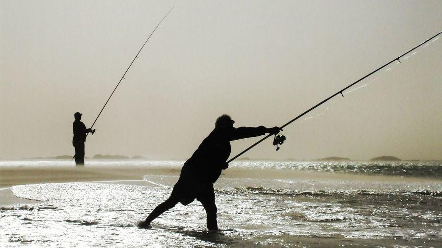 Silhouette man fishing in sea against sky