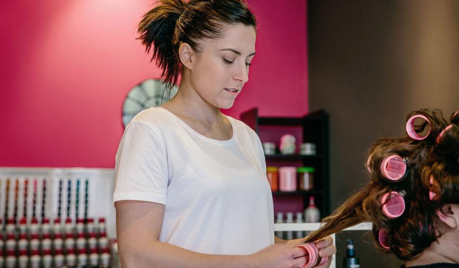Female hairdresser styling customer hair in salon