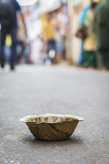 banana vessel waste put on street maket, Pushkar, India Bazaar Blur Background Close-up Day Floor Focus On Foreground Garbage Indiapictures Marketplace Outdoors Selective Focus Street Surface Level Trash Waste