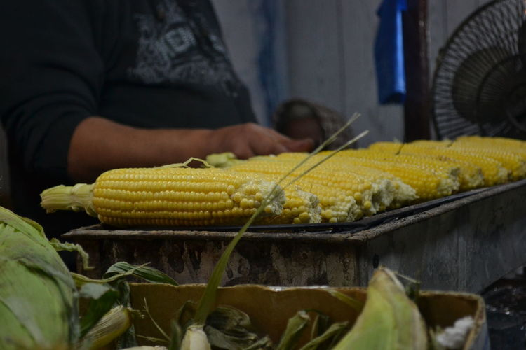 Midsection Of Vendor By Sweetcorns For Sale At Market Stall