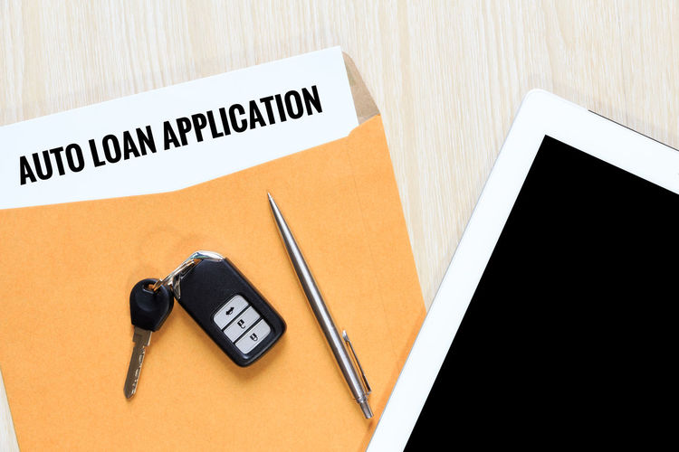 Digital Tablet With Loan Application Form And Car Key On Table