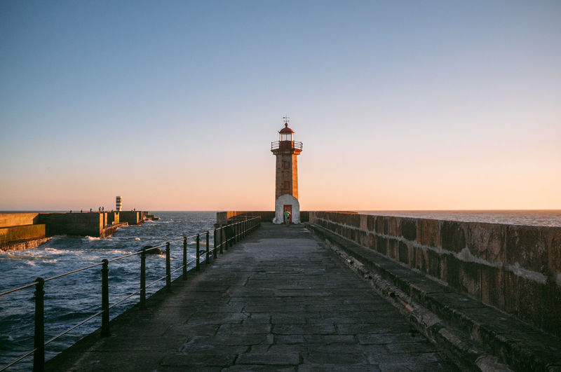 Scenic View Of Lighthouse On Pier At Sunset