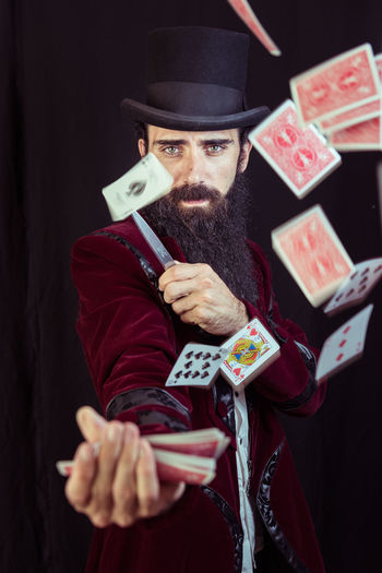 Portrait of magician throwing cards against black background