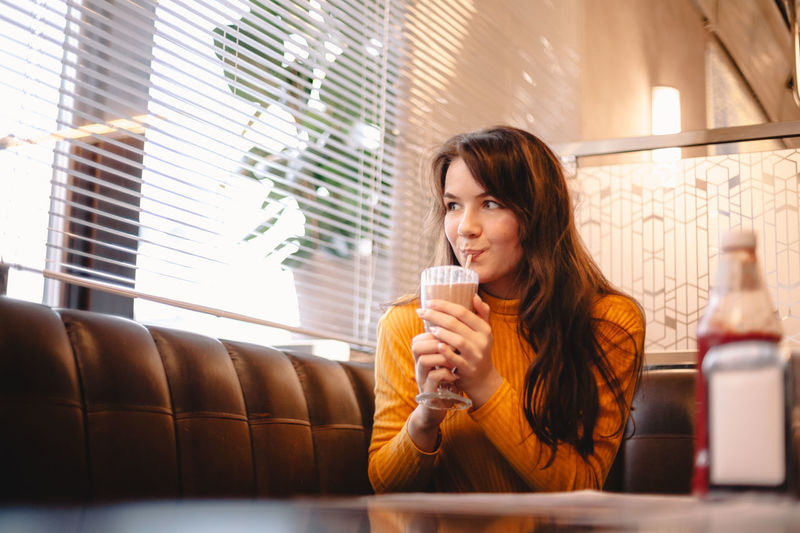 Young woman drinking coffee in glass window