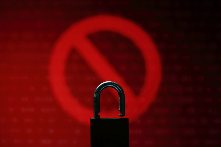 Close up open padlock infront of red no entry sign light and digital binary code