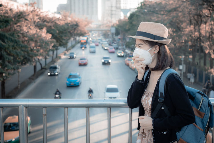 Young woman wearing mask standing on footbridge