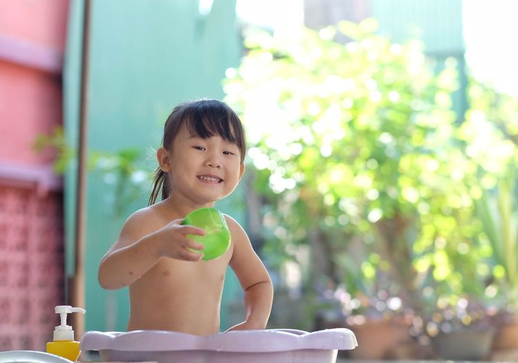 Little girl playing water in the plastic basin happily in the garden. Playing Water Bath Bathtub Tub Basin Girl Child Kids Cute Bathtub Child Childhood One Person Smiling Focus On Foreground Sitting Innocence Portrait Happiness Cute Shirtless Day Real People Looking Looking At Camera Lifestyles Table Outdoors
