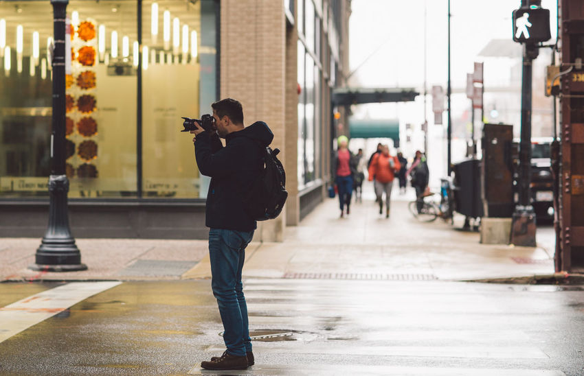 Technology Wireless Technology Photographing Real People Holding Photography Themes Full Length One Person Architecture City Communication Mobile Phone Activity Lifestyles Smart Phone Incidental People Camera - Photographic Equipment Connection Focus On Foreground Outdoors Photographer Digital Camera