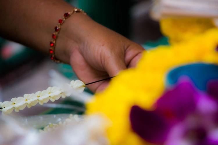 Cropped hand making garland at flower market
