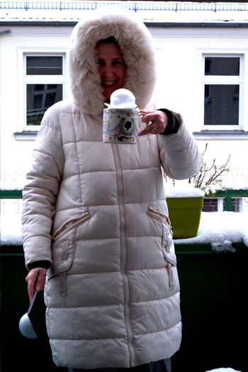 Full length of senior woman photographing while standing in winter