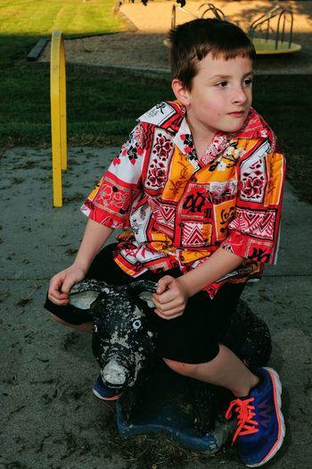 Boy sitting on equipment at playground