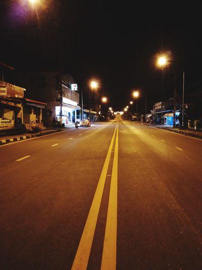 Empty road along illuminated street lights at night