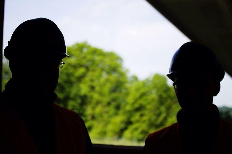 Two Men In Silhouette, Wearing Hard Hats