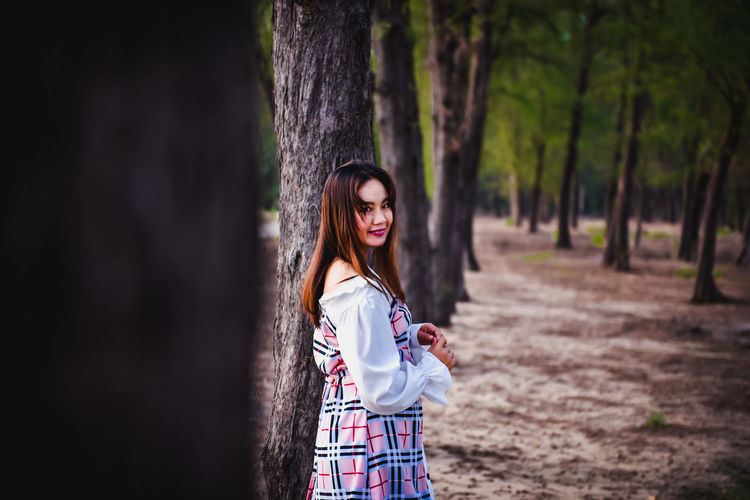 Portrait of woman standing by tree trunk in forest