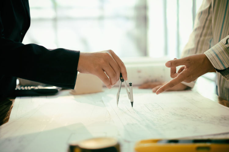 Close-Up Of Businessmen Working With Compass At Desk
