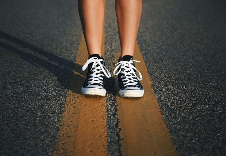Low section of woman standing on double yellow line