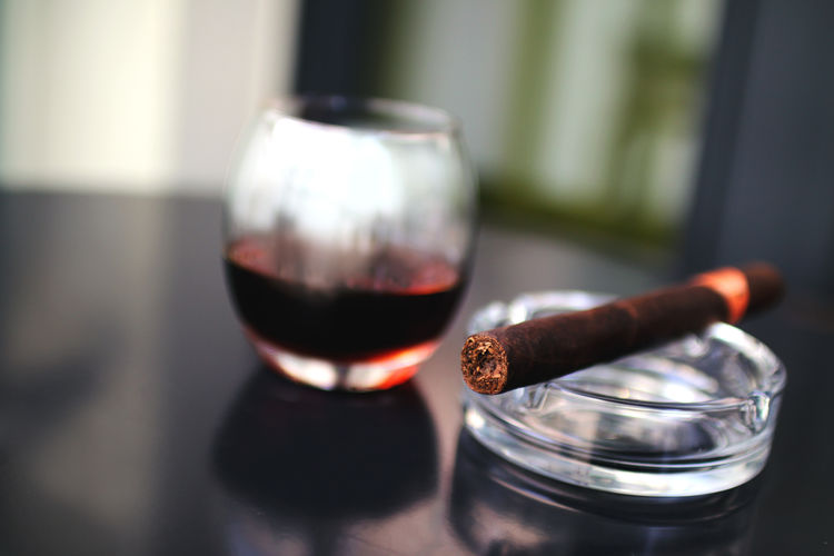 Close-Up Of Cigar And Red Wine In Glass On Table