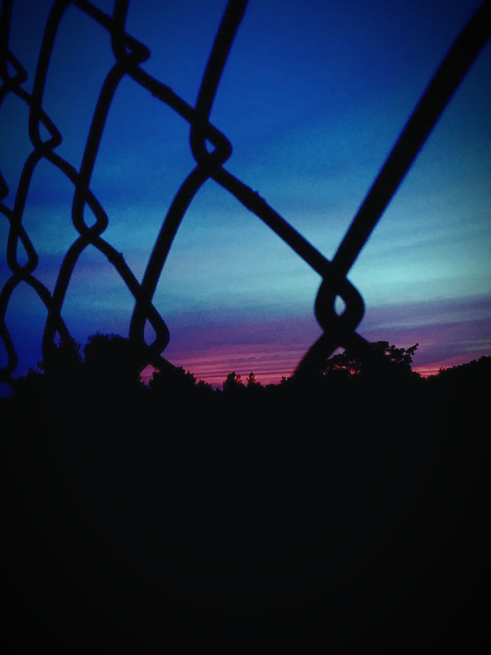 SILHOUETTE OF CHAINLINK FENCE AGAINST SKY DURING SUNSET