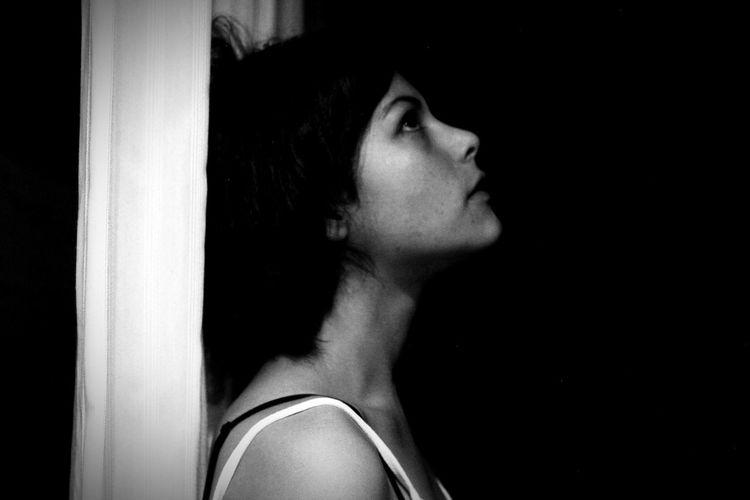 Close-up of girl looking up in darkroom
