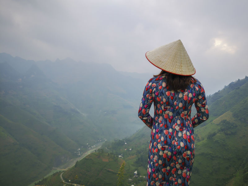 Young Vietnamese women facing and pose for camera with stunning view of the Nho Que river surrounded by mountains from the Ma Pi Leng pass in northern Vietnam Mountain Cloudy Green Color Meo Vac Vietnam Vietnamese Adult Ao Dai Beauty In Nature Clothing Day Hat Idyllic Landscape Leisure Activity Lifestyles Looking At View Mountain Mountain Range Nature One Person Outdoors People Pose Real People Scenics - Nature Standing Sunrise Three Quarter Length Traditional Dress Tranquil Scene Tranquility Valley Women