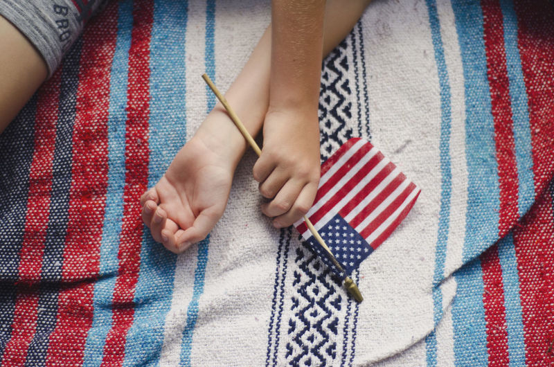 High angle view of hand holding american flag while lying on bed