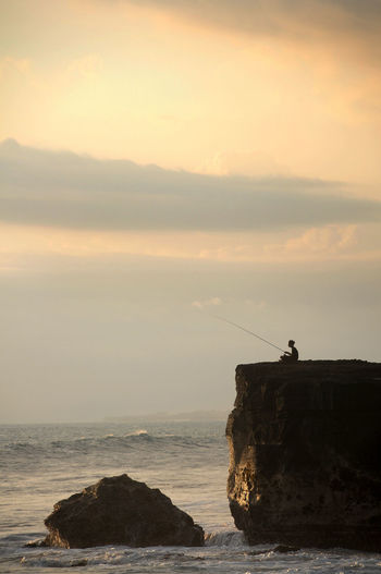 Silhouette Person Fishing By Sea Against Sky During Sunset