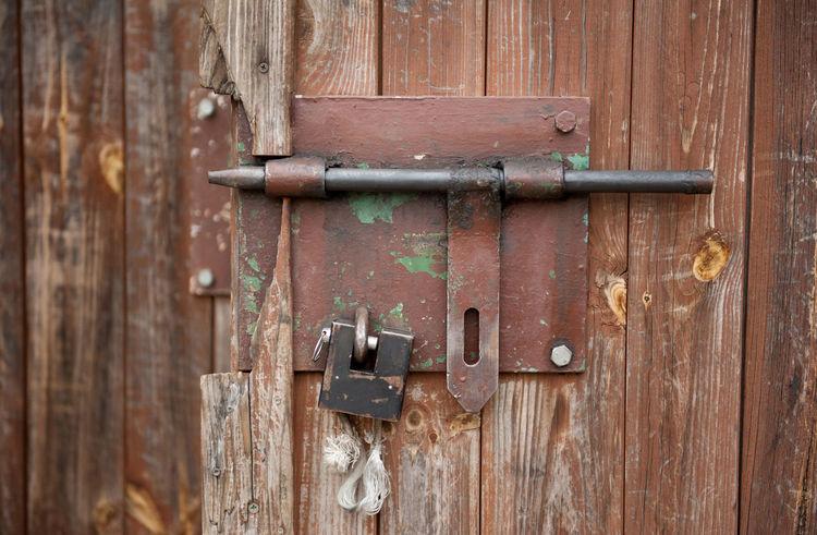 Iron sliding bolt unlocked and padlock in old wooden door of shed in horizontal orientation, nobody. Bolt Door Door Lock Doors Latch Lock Metal No People Padlock Plank Protection Rusty Shed Sliding Unlocked Wood Wooden
