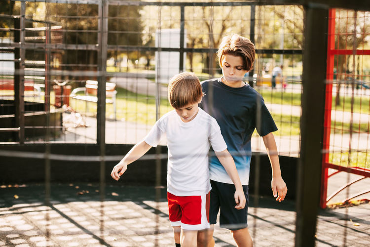 Two cute teenagers play soccer on the freestyle soccer field. boys fight for the ball in the game.